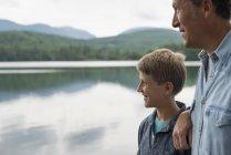 Отец и сын стоял на открытом воздухе на берегу озера и глядя на вид — стоковое фото