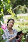 Giovane donna in serra vivaio organico utilizzando tablet digitale . — Foto stock