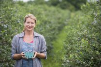Woman holding container of blueberries at organic farm. — Stock Photo