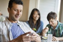 Mid adult man using smartphone at cafe table with people eating in background. — Stock Photo