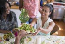 Groupe de femmes partageant la salade pendant le dîner dans la cuisine de campagne intérieure . — Photo de stock