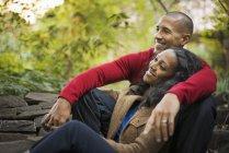 Взрослая пара, сидящая рядом под деревьями в городском парке . — стоковое фото