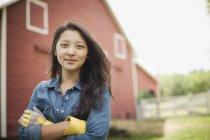 Giovane donna in piedi di fronte alla tradizionale casa di campagna . — Foto stock