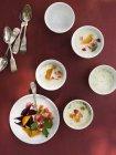 Mesa puesta con tazones blanco redondo de alimento fresco sobre fondo rojo. - foto de stock