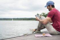 Vista lateral del hombre sentado en el embarcadero lago y usar la tableta digital. - foto de stock