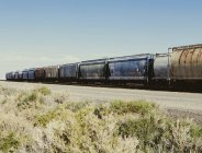Industrial train moving through rural field. — Stock Photo