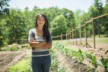 Молода жінка, стоячи з руки перетнув традиційні фермі в сільській місцевості — стокове фото