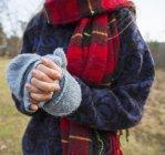 Vue recadrée de la femme avec écharpe en tartan réchauffant les mains par temps froid . — Photo de stock
