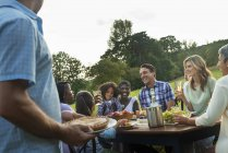 Group of family and friends sitting at table outdoors and having dinner. — Stock Photo