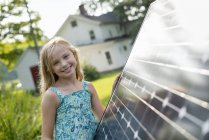 Elementary age girl posing beside solar panel in farmhouse garden. — Stock Photo