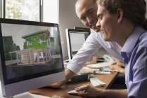 Architects discussing green construction project on computer monitor in office. — Stock Photo