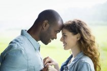 Young couple standing face to face and holding hands in green field and looking at each other. — Stock Photo