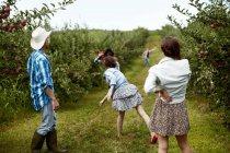 Молоді чоловіки і жінки, кидали фрукти на дорозі сільській місцевості. — стокове фото