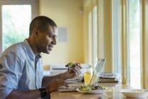 Uomo che lavora sul computer portatile mentre pranza al tavolo del caffè . — Foto stock