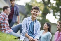 Pre-adolescent boy sitting on grass at summer party with family. — Stock Photo