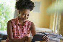Femme adulte moyenne utilisant une tablette numérique à la table dans un café . — Photo de stock