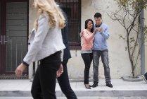 Paar nehmen Selfie mit Smartphone mit Menschen zu Fuß durch. — Stockfoto