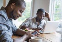 Zwei Männer mit Laptop und Smartphone am Tisch in Café. — Stockfoto