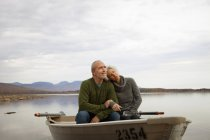 Mature man and woman sitting in rowing boat on water of autumnal lake. — Stock Photo