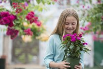 Pre-adolescent girl holding potted flowers at organic plant nursery and looking down. — Stock Photo