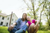 Mother with daughter sitting side by side in farmhouse green garden. — Stock Photo