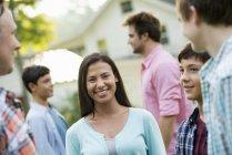 Група дорослих і підлітків постановки на літній вечірки в саду — стокове фото