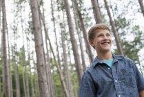 Vue faible angle de garçon debout parmi les arbres dans la forêt. — Photo de stock