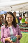 Young woman holding punnet of blueberries at farmer market stand. — Stock Photo