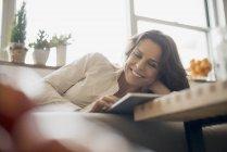 Donna a casa con tablet digitale sul divano . — Foto stock