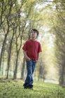 Menino pré-adolescente na floresta olhando para cima curiosamente . — Fotografia de Stock