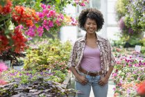 Woman standing in plant nursery surrounded by flowering plants and green foliage. — Stock Photo