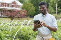 Молодой человек использует цифровой планшет в органических садоводческих питомниках . — стоковое фото