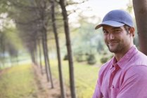 Man in cap leaning against tree in park and looking in camera. — Stock Photo