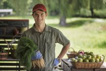 Young man holding bunch of fresh carrots at market farm stand. — Stock Photo