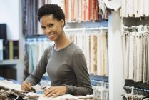 Cheerful woman working in textile design shop. — Stock Photo