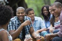 Amis jeunes joyeux d'avoir boissons, parler et rire dans le jardin de campagne. — Photo de stock