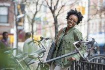 Mulher encostado corrimão ao lado de bicicleta rack com homens falando em plano de fundo — Fotografia de Stock