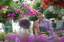 Young woman carrying stack of pots at flower plant nursery. — Stock Photo