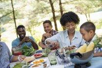 Дорослі та діти сидять навколо пікніку таблиці з харчування на відкритому повітрі. — стокове фото