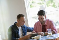 Two men using digital tablet together at cafe table. — Stock Photo