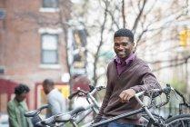 Meu jovem, apoiando-se na bicicleta rack e sorrindo na câmera — Fotografia de Stock