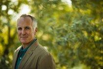 Зріла людина в зеленому сорочки і куртки в woodland себе. — стокове фото