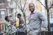 Homem adulto médio apoiando-se na bicicleta rack e sorrindo com as pessoas no fundo — Fotografia de Stock