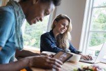 Deux femmes dans un café en utilisant une tablette numérique et un ordinateur portable pendant le déjeuner . — Photo de stock