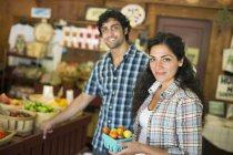 Young man and woman with container of ripe tomatoes at organic farmer store. — Stock Photo