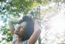 Jovem mulher em vestido florido com as mãos na cabeça, sorrindo e olhando para cima na floresta . — Fotografia de Stock