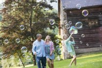 Parents watching daughter catching soap bubbles and laughing in countryside. — Stock Photo