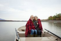 Mature man and woman sitting in rowing boat wrapped in warm blanket. — Stock Photo