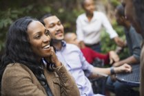 Gruppe von fröhlichen Freunden zusammensitzen im grünen Park und sprechen — Stockfoto