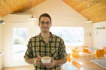 Молода людина, стоячи і проведення чашку кави у кав'ярні. — стокове фото